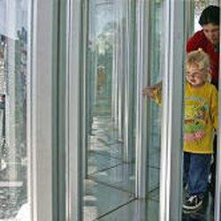 Celeste Camomile, in yellow, is helped through the glass maze by Davis Amusement's Michelle Poulsen.