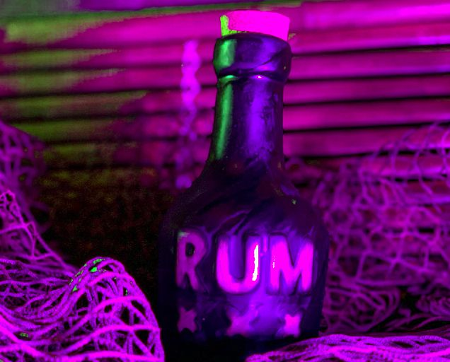 A black bottle with a stopper sits in a bunch of netting in purple light. The bottle says Rum XXX on it.