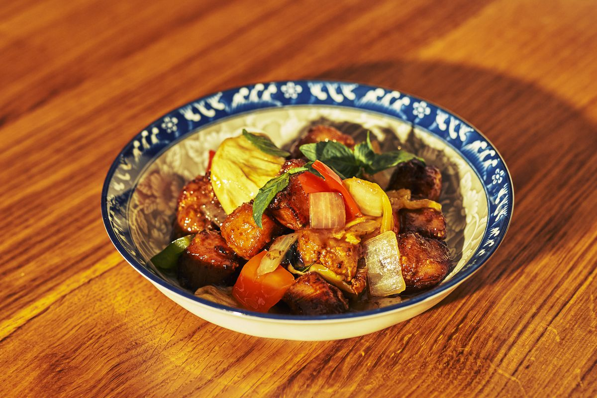 A blue-and-white ceramic bowl filled with sweet-and-sour pork accented by colorful vegetables sits on a wooden table.