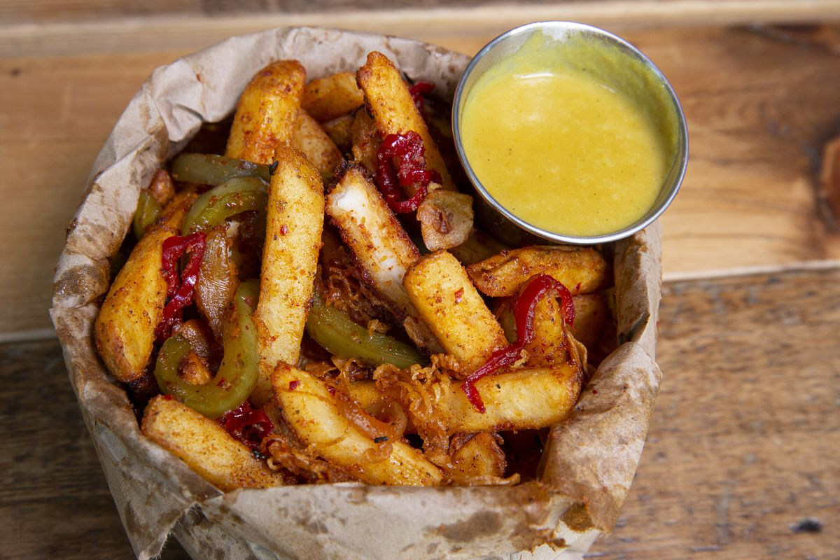 A paper bag full of fries, a metal cup will with mustard sauce.
