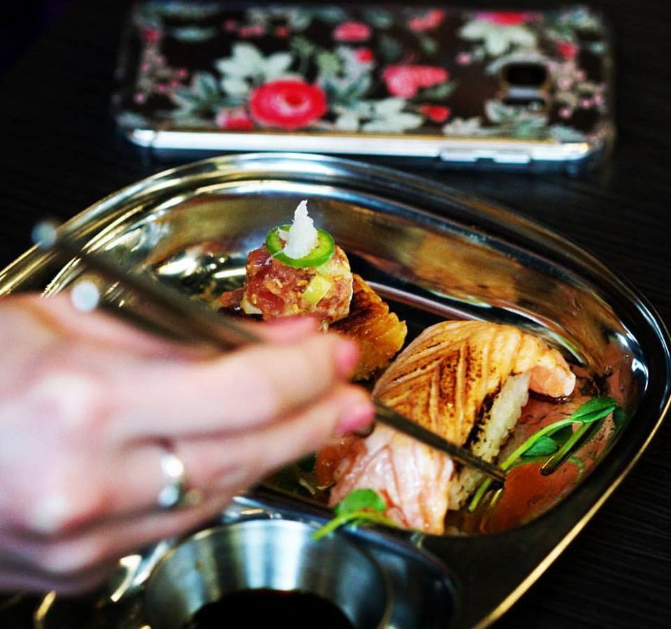A hand picking up charred salmon from a silver tray