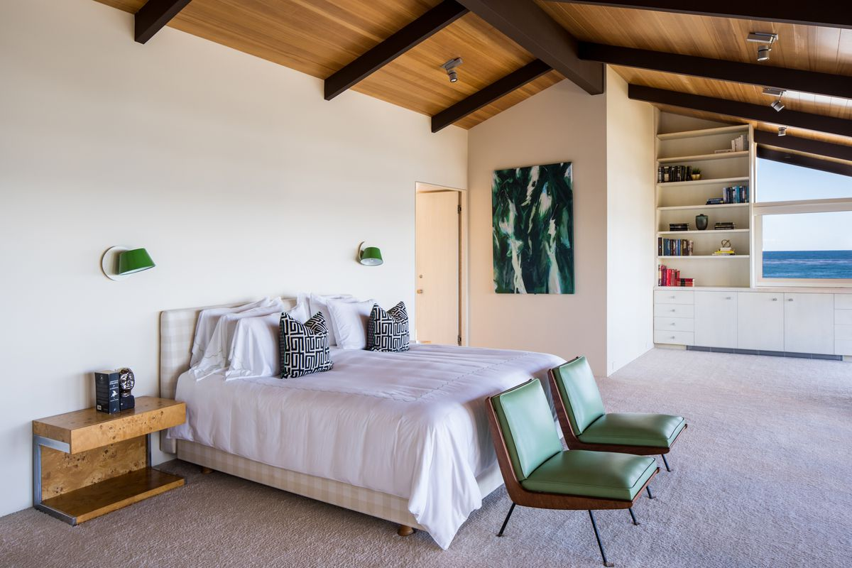 A bedroom with an A-frame style ceiling, exposed beams, and white bed.