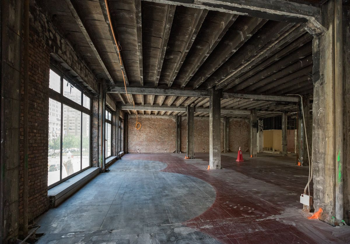 A large open space with exposed concrete and beams.  One wall has exposed red brick.  There are orange cones on the floor in various places.