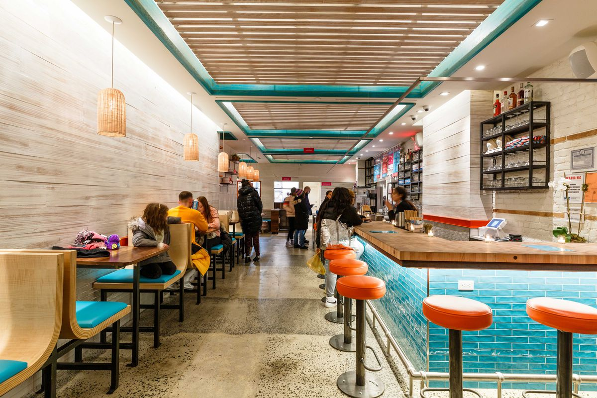 Orange bar stools sit juxtaposed against sea blue tiles and booth cushions