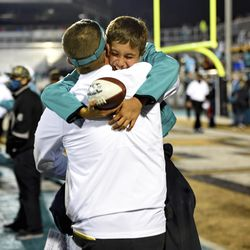 Coastal Carolina head coach Jamey Chadwell, back, hugs his son Jameson after an NCAA college football game against BYU, Saturday, Dec. 5, 2020, in Conway, S.C.