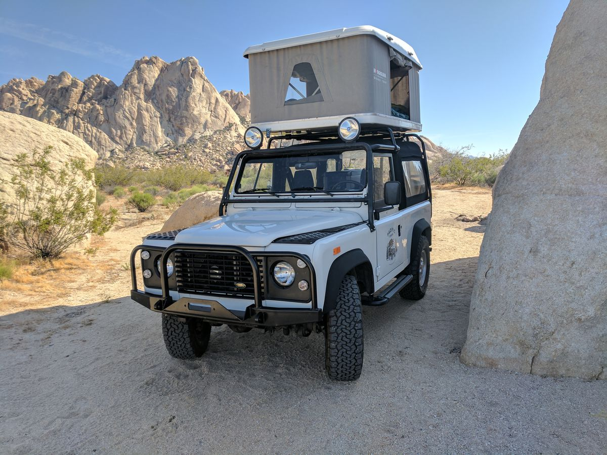 A Land Rover Defender parked with a rooftop tent in the desert.