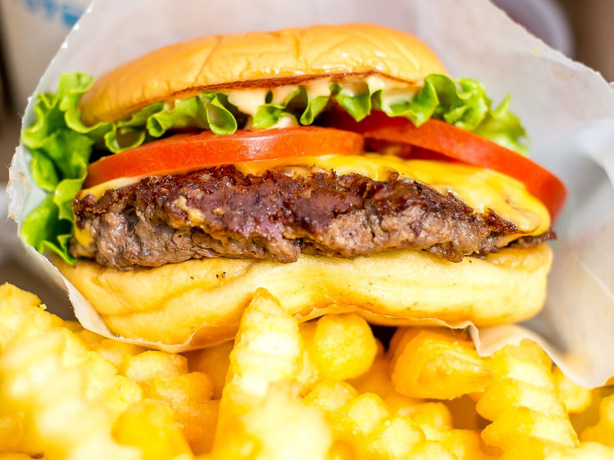 A Shake Shack burger in paper wrapping rests on top of crinkly fries