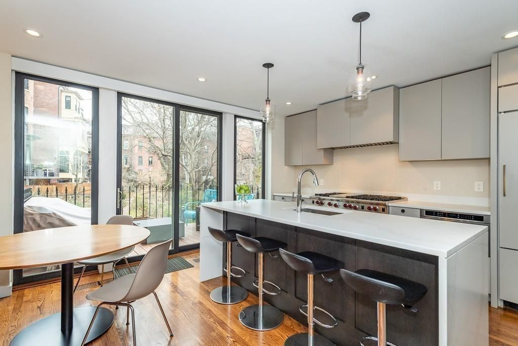 A kitchen with a table and chairs and an island right next to it with four stools in front.
