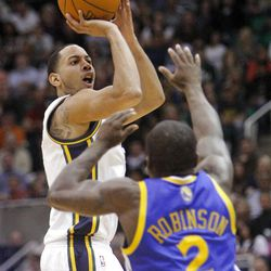 Utah Jazz guard Devin Harris (5) puts up a three point shot over Golden State's #2 Nate Robinson as the Utah Jazz and the Golden State Warriors play Friday, April 6, 2012 in Salt Lake City. Jazz won 104-98.
