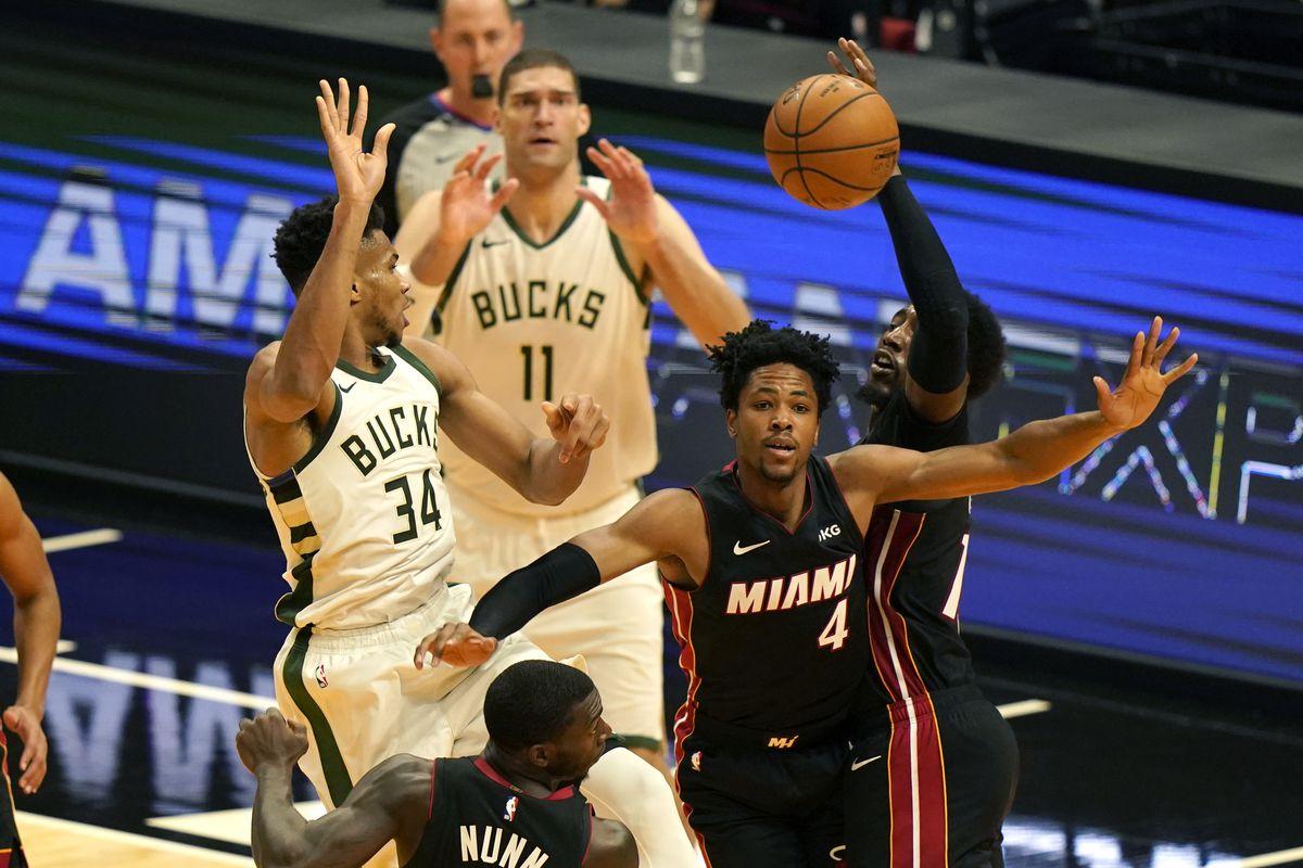 Miami Heat center Bam Adebayo, right, blocks a pass by Milwaukee Bucks forward Giannis Antetokounmpo (34) during the first half of an NBA basketball game, Tuesday, Dec. 29, 2020, in Miami. At right is Miami Heat forward KZ Okpala (4).