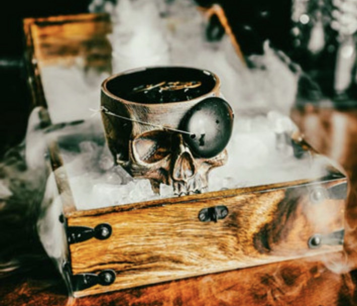 A metal skull glass with an eyepatch, surrounded by dry ice