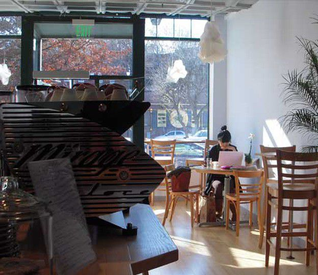 A small cafe with wooden tables and chairs, a large espresso machine in the foreground and a view out the front window