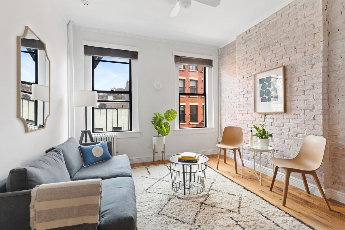 A living area with exposed brick, two large windows, a ceiling fan, hardwood floors, and a grey couch.