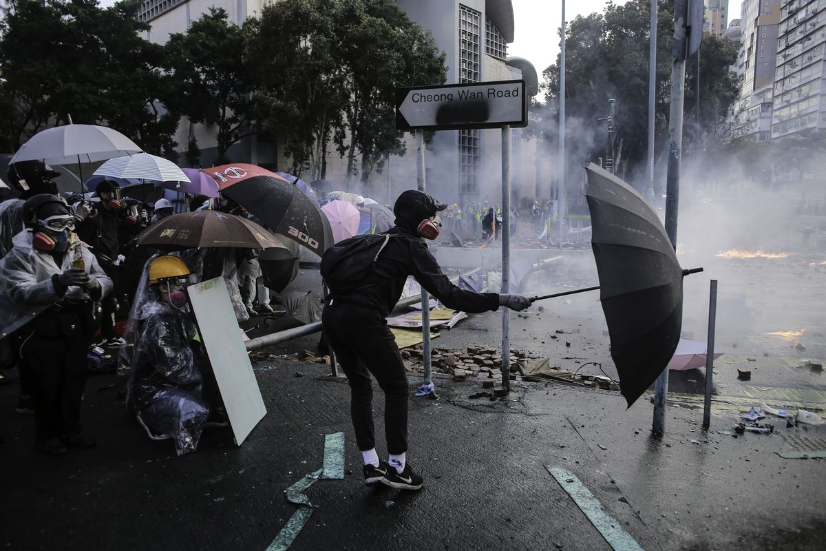 Protesters use umbrellas as shields during the demonstration...
