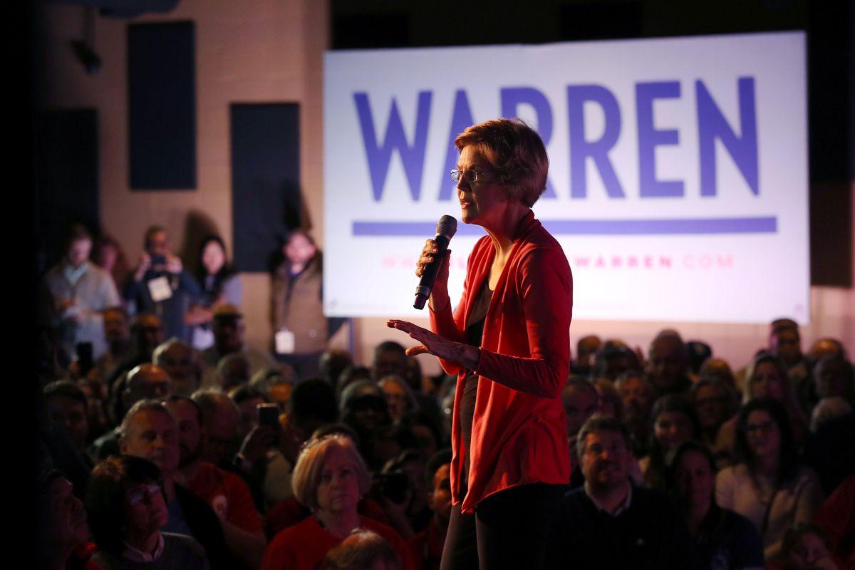 "Senator Elizabeth Warren speaks into a microphone in front of a campaign sign that says ""Warren."""