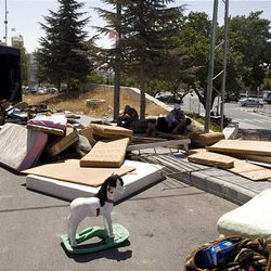 Israeli workers unload the belongings of a Palestinan family in a street after they were evicted from their house in the east Jerusalem neighborhood of Sheikh Jarrah Sunday.