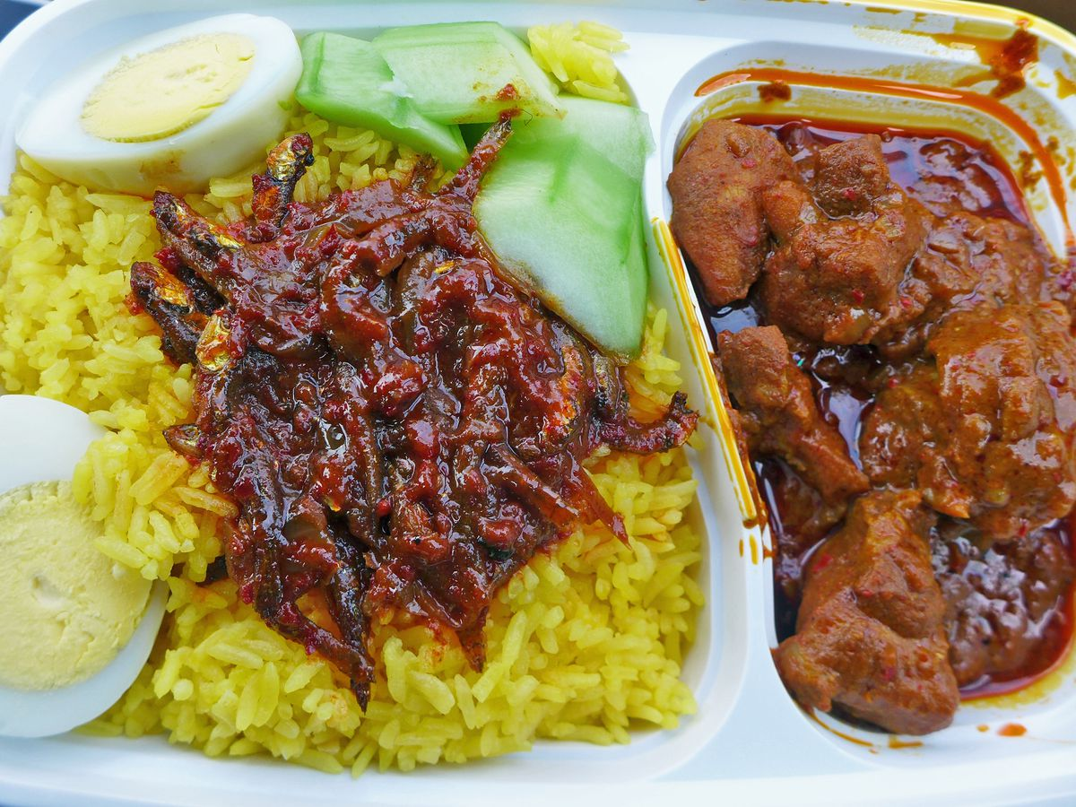 Yellow rice in a white compartment tray, with a dark chicken curry in one part, and brown relish, cucumber, and split boiled egg on top of the rice in the other.