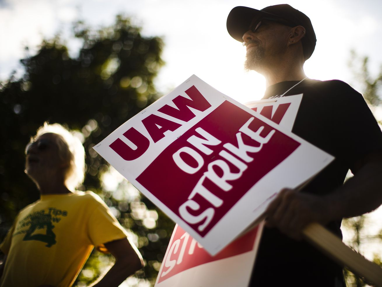 """Union members carry pickets signs that read """"UAW on strike."""""""