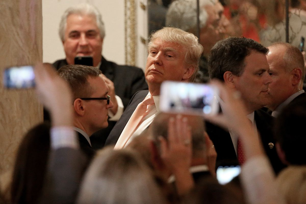 Republican presidential candidate Donald Trump looks at reporters shouting questions to him after he delivered remarks at primary night event at the Mar-A-Lago Club's Donald J. Trump Ballroom March 15, 2016, in Palm Beach, Florida.