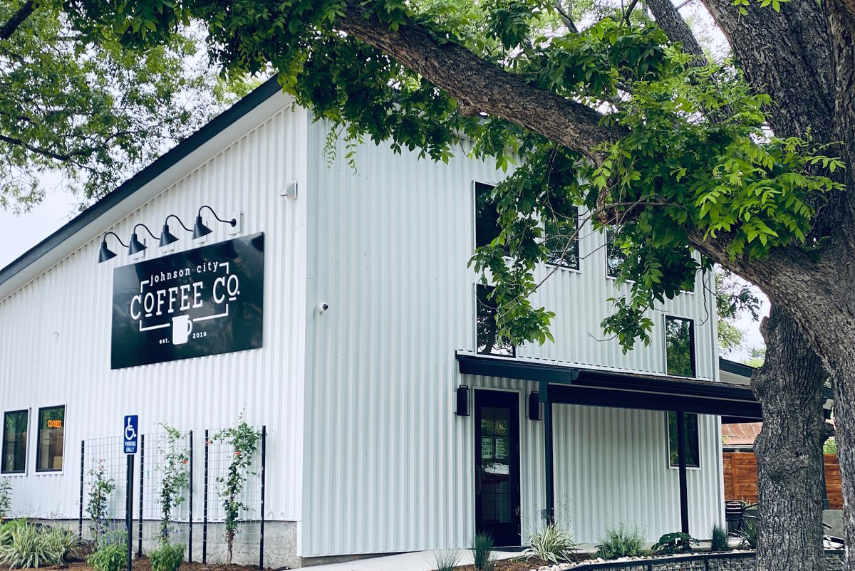 A white building with a black sign reading Johnson City Coffee Co.