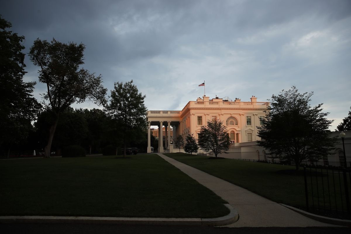 In this June 17, 2018, file photo, the White House is seen illuminated by the setting sun with storm clouds nearby in Washington. One month ago Friday, an unidentified Trump administration official set off a White House firestorm by claiming in a New York