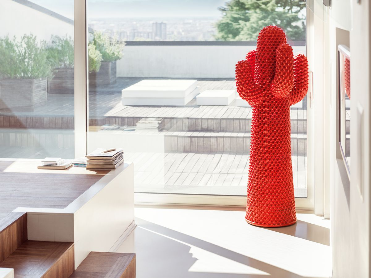 A red cactus large coat hanger, inside of a modern home.