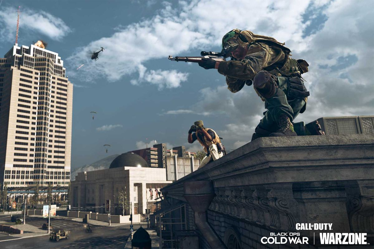 A Call of Duty: Warzone player sits on a rooftop in front of Nakatomi Plaza