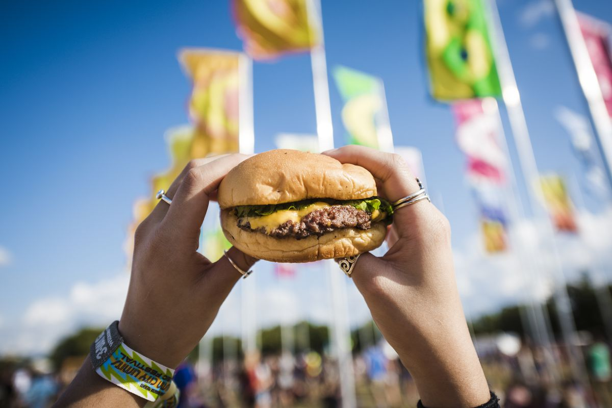 A hand holding up a burger in front of a music festival crowd