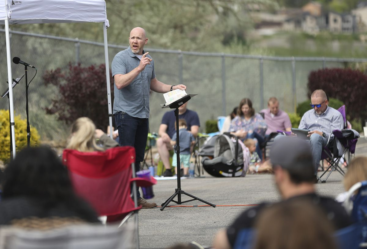"The Mission Church Pastor Rich Sanford speaks during worship in a ""COVID-friendly"" service in the church parking lot in South Jordan on Sunday, May 3, 2020."