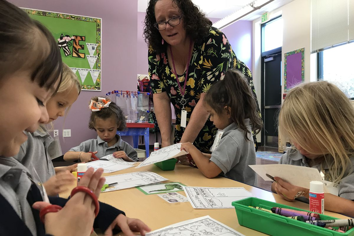 Mary Ann Mahoney helps her preschool students with a cutting and pasting lesson.