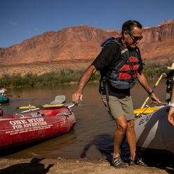 Sen. Mitt Romney, R-Utah, helps pull a raft onto the shore while he floats a section of the Colorado River northeast of Moab on Saturday, Sept. 18, 2021.