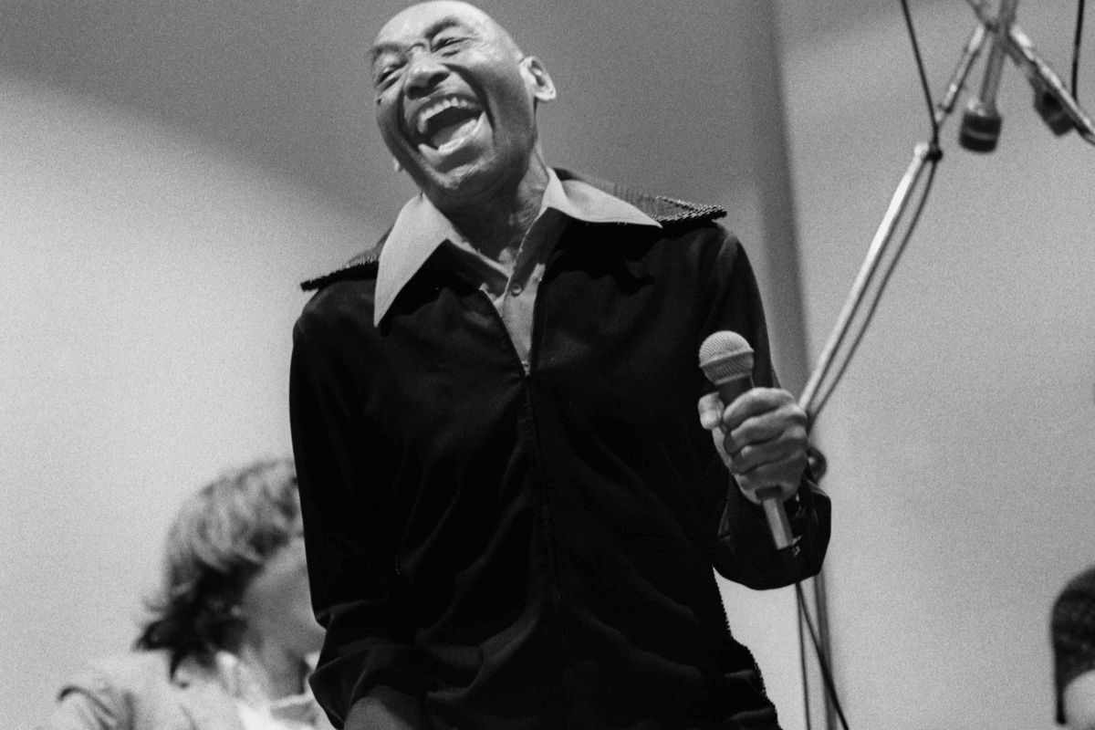 Frankie Manning holding a microphone and laughing