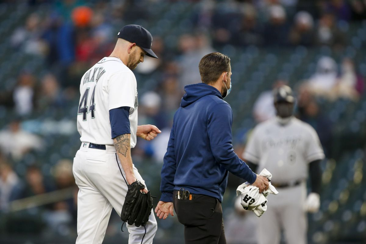 Seattle Mariners starting pitcher James Paxton leaves the mound with a team trainer following an injury during the second inning against the Chicago White Sox at T-Mobile Park.