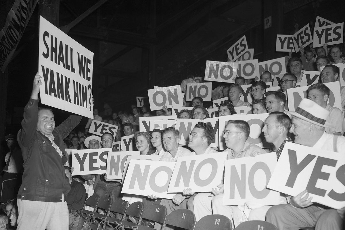 Man Holding Sign near Grandstand Audience