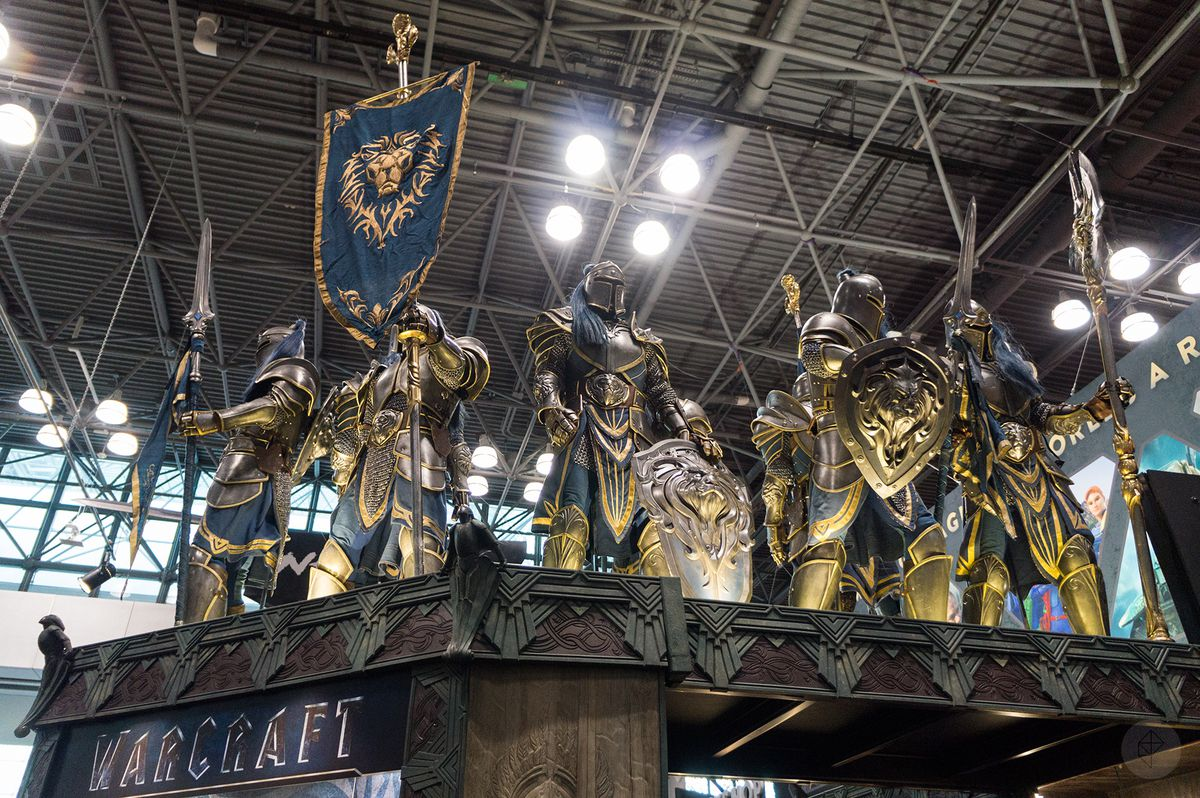 a group of life-size Alliance soldiers from the Warcraft movie carrying the Alliance banner perched atop the Weta Workshop booth at NYCC 2015