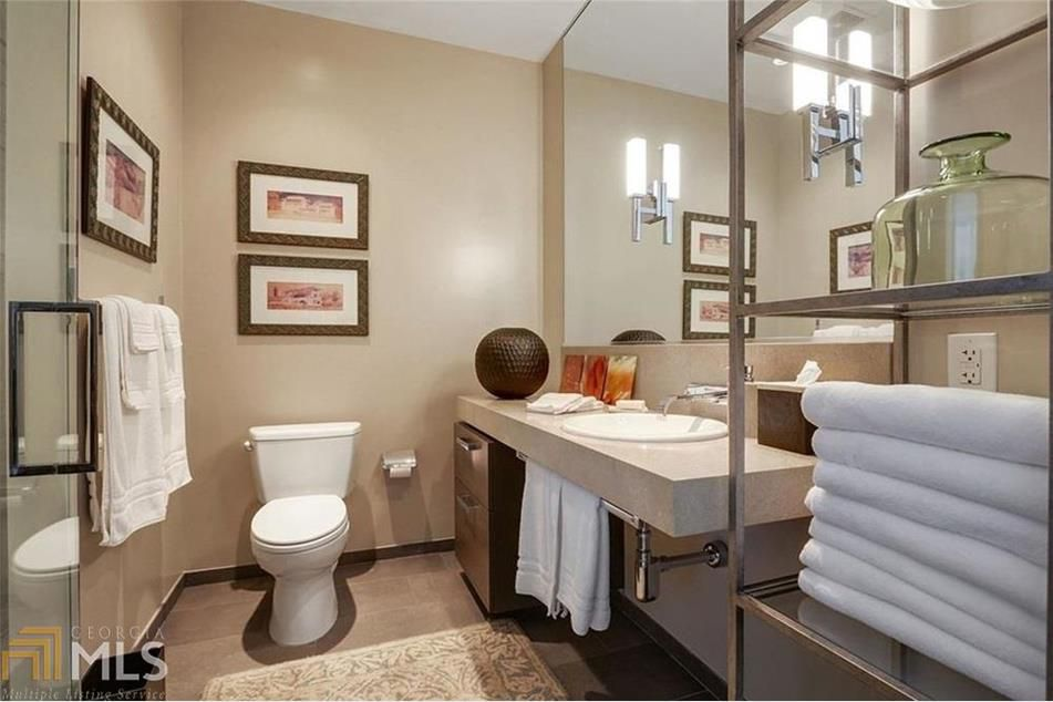 A beige bathroom with towels and cabinetry at right.