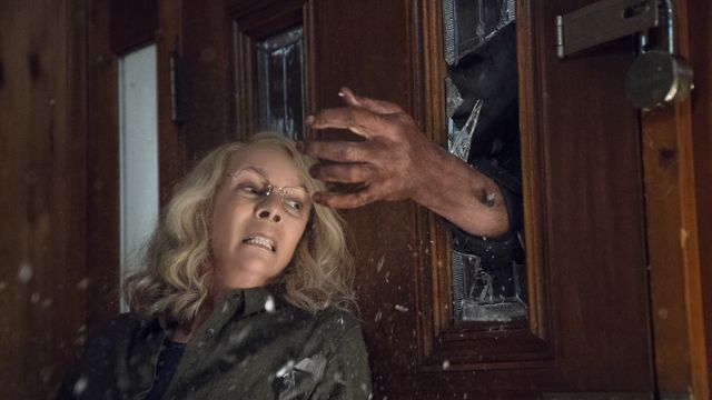 Laurie Strode (Jamie Lee Curtis) dodging Michael Myers's hand as it comes through the door in the 2018 film Halloween.