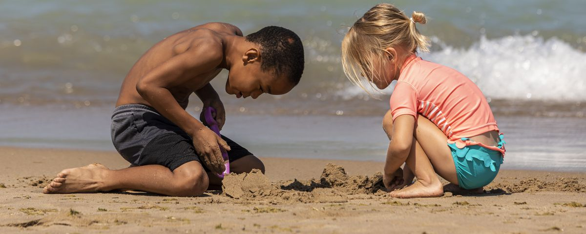 Isaiah Flowers, 7, builds a sand castle with 4-year-old Mara Dues at 31st Street Beach on the South Side.