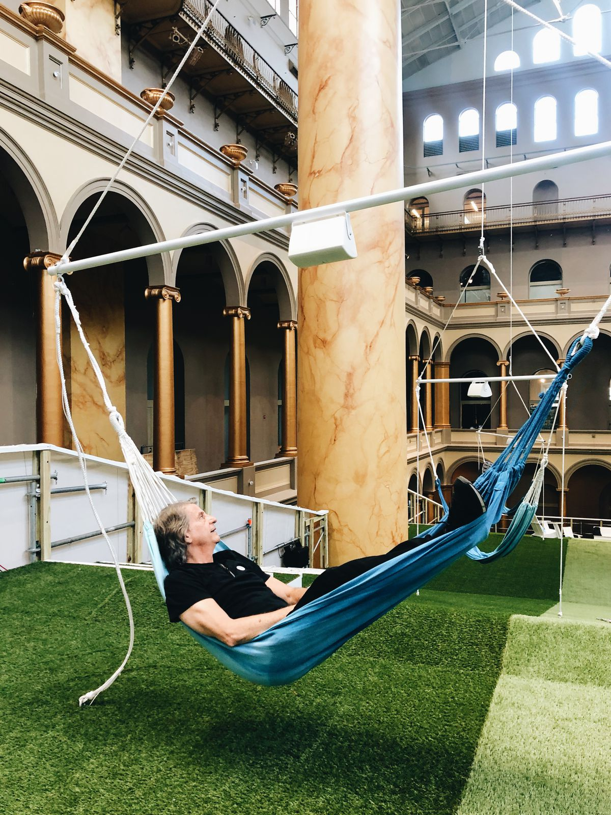 A man lies back on a blue hammock in a courtyard. He is looking at the building's arches and columns.