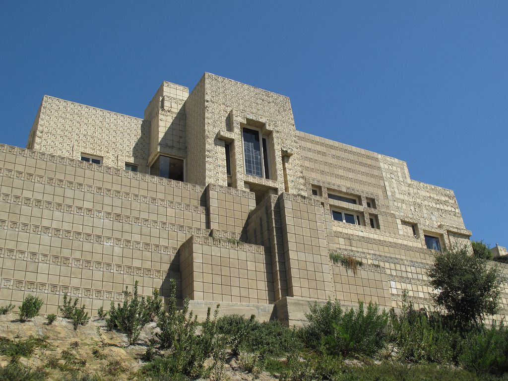 The Ennis House by Frank Lloyd Wright. The facade is tan brick. The building is tall and it situated on a hillside.