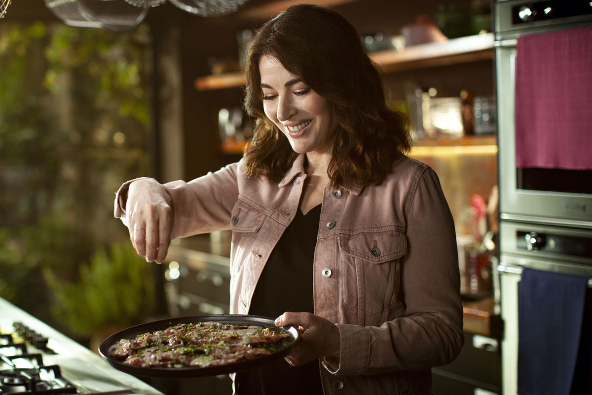 Nigella Lawson seasons a plate of food on 'Cook Eat Repeat,' her new BBC cooking show