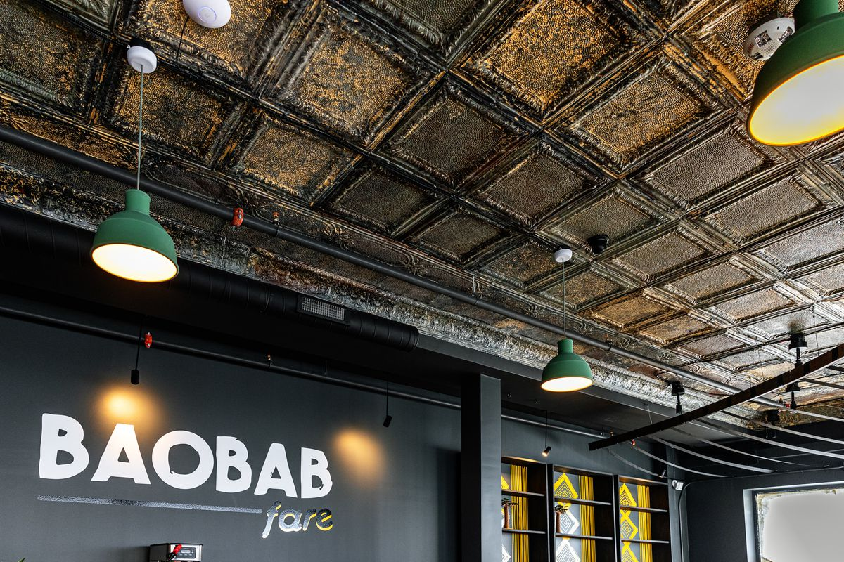 The old tin ceiling remains a prominent design feature at Baobab Fare in Detroit. Two midcentury inspired green light fixtures hang from the ceiling over the bar. Baobao Fare painted in white, black and yellow against a gray wall
