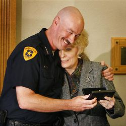 Salt Lake Police Chief Chris Burbank hugs Robyn Salmon, a security officer at Grand America Hotel, whose quick action may have prevented a deadlier incident.
