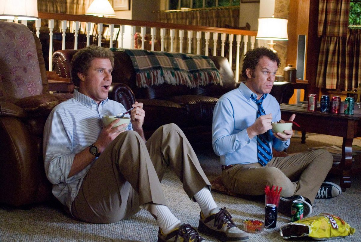 Brennan (Ferrell) and Dale (Reilly) excitedly watch TV.