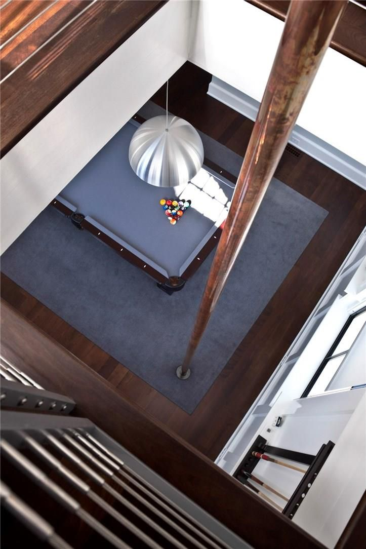 A fireman's pole goes down into a lower floor with a gray rug and pool table.