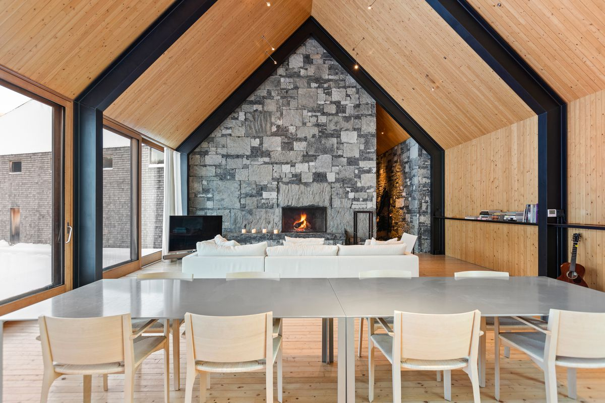 A living room has a dining room table that opens up to a white couch and a stone wall with fireplace.