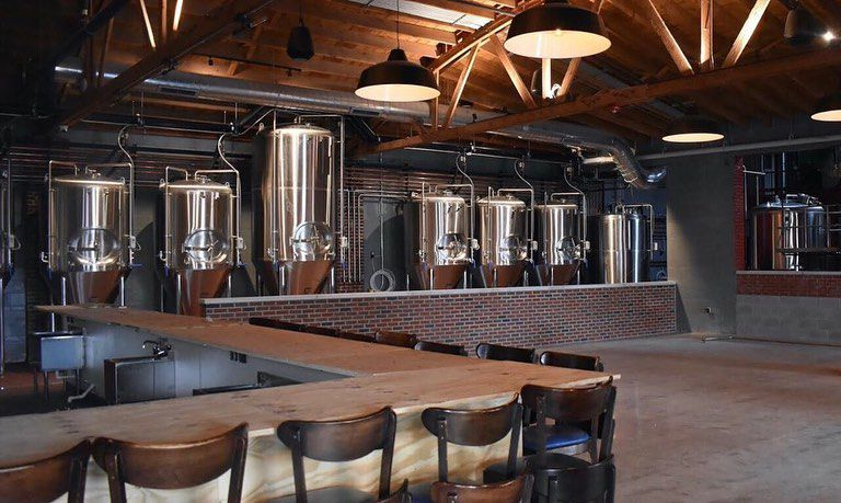 A line of huge silver fermentation tanks sit against an exposed brick wall.