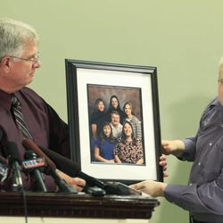 Chuck Cox, right, the father of Susan Powell, who was reported missing Dec. 7, 2009, in Utah, is helped by family friend Michael Gifford, left, as he talks to reporters about a photo of his family, with Susan Cox shown at upper right, Thursday, Dec. 17, 2009, in Puyallup, Wash. Powell's family said Thursday they are saddened but not surprised that her husband Josh Powell has been named a person of interest in the investigation.