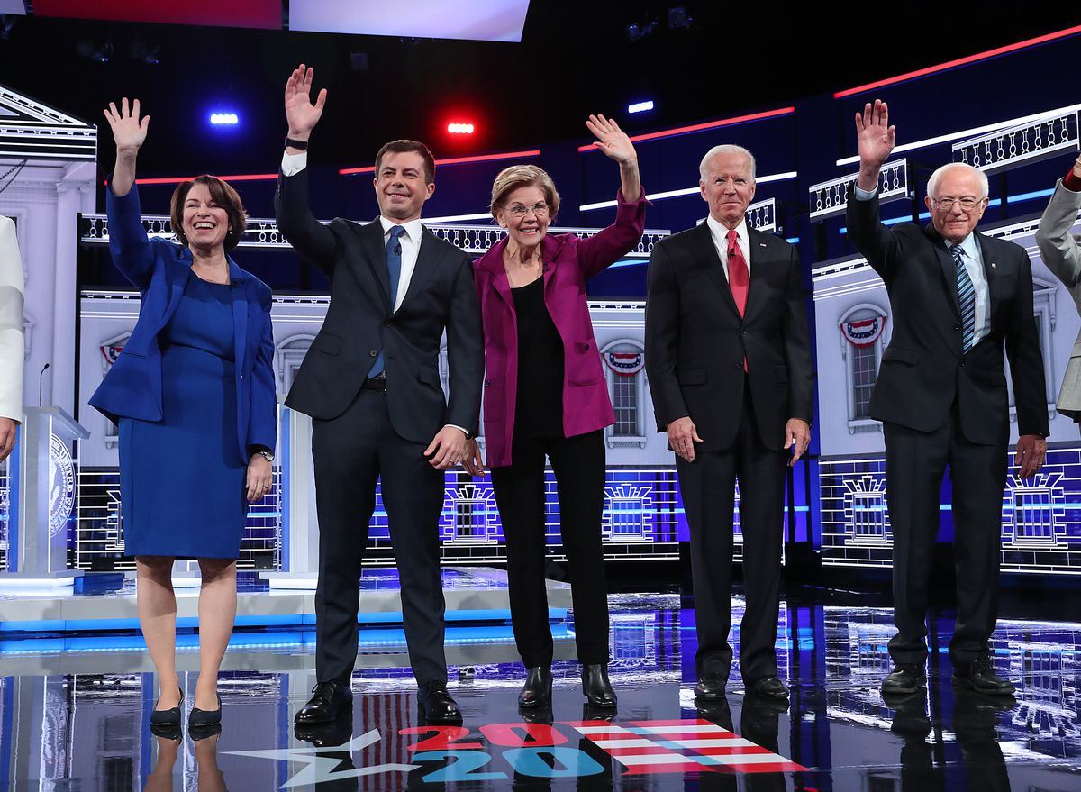 Senator Amy Klobuchar, former South Bend Mayor Pete Buttigieg, Senator Elizabeth Warren, former Vice President Joe Biden, and Senator Bernie Sanders waving to the debate crowd.
