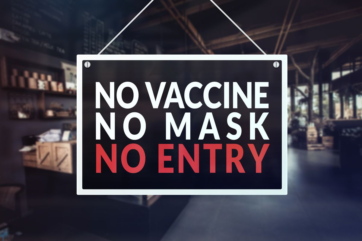 """A large sign in all caps says """"No Vaccine, No Mask, No Entry"""" with a blurry restaurant in the background."""